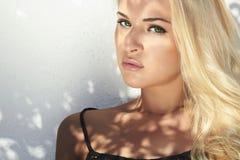 Όμορφη ξανθή γυναίκα στο φως της ημέρας σκιές στο πρόσωπο κορίτσι κοντά στον άσπρο τοίχο πρότυπη κορυφή Στοκ Φωτογραφία
