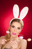 Όμορφη ξανθή γυναίκα ως λαγουδάκι Πάσχας με τα αυτιά κουνελιών στο κόκκινο υπόβαθρο, πυροβολισμός στούντιο Νέα κυρία που κρατά τρ Στοκ Φωτογραφίες