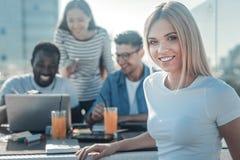 Όμορφη ξανθή γυναικεία συνεδρίαση με τα groupmates στον καφέ Στοκ φωτογραφία με δικαίωμα ελεύθερης χρήσης