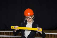 Όμορφη ξανθή επιχειρηματίας με τη σειρά εφαρμογής στο γραφείο σοφιτών στο πορτοκαλιά κράνος και το κοστούμι κατασκευής Στοκ φωτογραφία με δικαίωμα ελεύθερης χρήσης