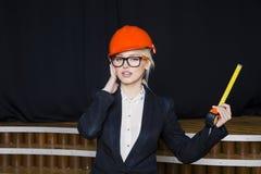 Όμορφη ξανθή επιχειρηματίας με το μέτρο ταινιών στο γραφείο σοφιτών στο πορτοκαλιά κράνος και το κοστούμι κατασκευής Στοκ Φωτογραφίες