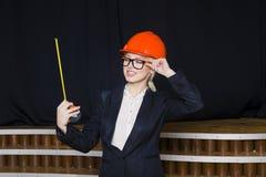 Όμορφη ξανθή επιχειρηματίας με το μέτρο ταινιών στο γραφείο σοφιτών στο πορτοκαλιά κράνος και το κοστούμι κατασκευής Στοκ Εικόνες