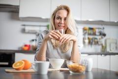 Όμορφη ξανθή καυκάσια τοποθέτηση γυναικών στην κουζίνα της, πίνοντας τον καφέ ή το τσάι και τρώγοντας ένα υγιές σύνολο γεύματος π Στοκ φωτογραφίες με δικαίωμα ελεύθερης χρήσης