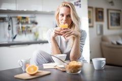 Όμορφη ξανθή καυκάσια τοποθέτηση γυναικών στην κουζίνα της, πίνοντας τον καφέ ή το τσάι και τρώγοντας ένα υγιές σύνολο γεύματος π Στοκ εικόνες με δικαίωμα ελεύθερης χρήσης