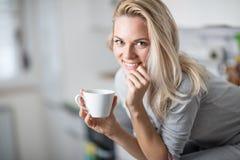 Όμορφη ξανθή καυκάσια τοποθέτηση γυναικών στην κουζίνα της, πίνοντας τον καφέ ή το τσάι και τρώγοντας ένα υγιές σύνολο γεύματος π Στοκ φωτογραφία με δικαίωμα ελεύθερης χρήσης