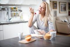 Όμορφη ξανθή καυκάσια τοποθέτηση γυναικών στην κουζίνα της, πίνοντας τον καφέ ή το τσάι και τρώγοντας ένα υγιές σύνολο γεύματος π Στοκ Φωτογραφίες