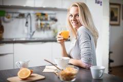 Όμορφη ξανθή καυκάσια τοποθέτηση γυναικών στην κουζίνα της, πίνοντας τον καφέ ή το τσάι και τρώγοντας ένα υγιές σύνολο γεύματος π Στοκ εικόνα με δικαίωμα ελεύθερης χρήσης