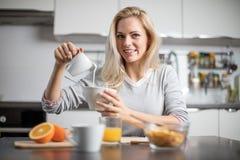 Όμορφη ξανθή καυκάσια τοποθέτηση γυναικών στην κουζίνα της, πίνοντας τον καφέ ή το τσάι και τρώγοντας ένα υγιές σύνολο γεύματος π Στοκ Εικόνα