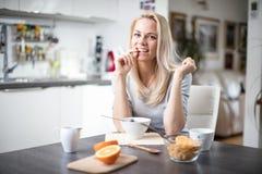 Όμορφη ξανθή καυκάσια τοποθέτηση γυναικών στην κουζίνα της, πίνοντας τον καφέ ή το τσάι και τρώγοντας ένα υγιές σύνολο γεύματος π Στοκ Φωτογραφία