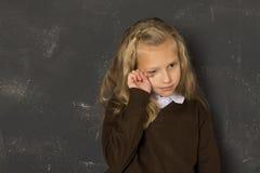 Όμορφη ξανθή μαθήτρια που φωνάζει λυπημένο ευμετάβλητο και που κουράζει μπροστά από τον πίνακα σχολικής τάξης Στοκ Φωτογραφία