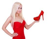 Όμορφη ξανθή νέα γυναίκα που κρατά το προκλητικό κόκκινο παπούτσι απομονωμένο Στοκ Φωτογραφία