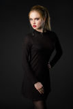 Όμορφη ξανθή νέα κυρία στο μαύρο φόρεμα στο μαύρο υπόβαθρο στοκ φωτογραφίες με δικαίωμα ελεύθερης χρήσης