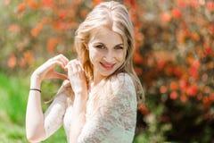 Όμορφη ξανθή παρουσιάζοντας μορφή καρδιών Κήπος Bloomig καλός καιρός Στοκ Εικόνα