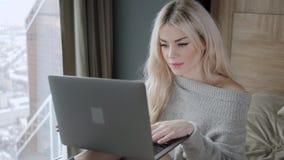 Όμορφη ξανθή συνεδρίαση γυναικών στο κρεβάτι με το γκρίζο lap-top αργιλίου Χαμόγελα κοριτσιών, καλή διάθεση Blogging, κοιτάζοντας φιλμ μικρού μήκους