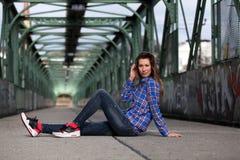 Όμορφη ξανθή συνεδρίαση γυναικών σε μια γέφυρα με τα γκράφιτι στοκ εικόνα