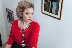 Όμορφη ξανθή τοποθέτηση γυναικών ενάντια στον τοίχο με τις εικόνες Στοκ εικόνα με δικαίωμα ελεύθερης χρήσης