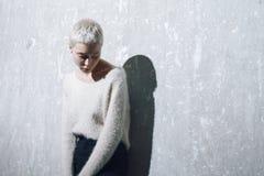 Όμορφη ξανθή τοποθέτηση κοριτσιών στο συμπαγή τοίχο Στοκ φωτογραφία με δικαίωμα ελεύθερης χρήσης