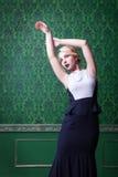 Όμορφη ξανθή τοποθέτηση στο εκλεκτής ποιότητας πράσινο εσωτερικό Στοκ Εικόνα