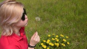 Όμορφη ξανθή φυσώντας πικραλίδα κοριτσιών απόθεμα βίντεο