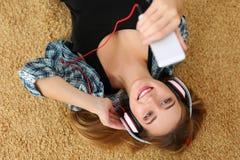 Όμορφη ξανθή χαμογελώντας γυναίκα που βρίσκεται στο πάτωμα ταπήτων που φορά το hea Στοκ Εικόνες