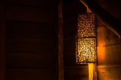 Όμορφη ξύλινη ένωση λαμπτήρων τοίχων στο ξύλινο κούτσουρο πέρα από το κρεβάτι στο εξοχικό σπίτι στην επαρχία στοκ εικόνες με δικαίωμα ελεύθερης χρήσης