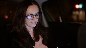 Όμορφη οδήγηση κοριτσιών σε ένα ταξί τη νύχτα και διαβασμένος την επιστολή στο smartphone απόθεμα βίντεο
