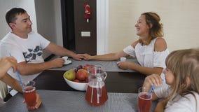 Όμορφη οικογένεια: η μητέρα, πατέρας και δύο κόρες μιλούν στο πρόγευμα μαζί στην κουζίνα στο σπίτι Γυναίκα με απόθεμα βίντεο