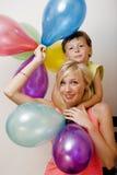 Όμορφη οικογένεια με τα μπαλόνια χρώματος στο λευκό Στοκ φωτογραφία με δικαίωμα ελεύθερης χρήσης