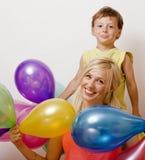 Όμορφη οικογένεια με τα μπαλόνια χρώματος στο λευκό Στοκ Φωτογραφίες
