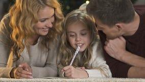 Όμορφη οικογένεια που βρίσκεται στο πάτωμα, γονείς που βοηθά λίγη κόρη για να γράψει τις επιθυμίες απόθεμα βίντεο