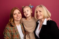 Όμορφη οικογένεια σε ένα στούντιο Κορίτσι με το mothe και γιαγιά στο ρόδινο υπόβαθρο στοκ εικόνα