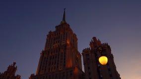 Όμορφη οικοδόμηση του Art Deco Παίρνει σκοτεινός, η πορτοκαλιά πρόσοψη τονίζεται πορφυρός ουρανός απόθεμα βίντεο