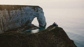 Όμορφη πίσω άποψη της ευτυχούς συνεδρίασης ανδρών και γυναικών που προσέχει κοντά τον ωκεανό ηλιοβασιλέματος πάνω από τον απότομο φιλμ μικρού μήκους