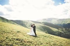Όμορφη πανέμορφη τοποθέτηση νυφών για να καλλωπίσει και κατοχή της διασκέδασης, τελετή πολυτέλειας στα βουνά με την καταπληκτική  Στοκ εικόνες με δικαίωμα ελεύθερης χρήσης