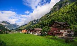 Όμορφη πανοραμική άποψη καρτών του γραφικού αγροτικού τοπίου βουνών στις Άλπεις με τα παραδοσιακά παλαιά αλπικά σαλέ βουνών Στοκ Εικόνες