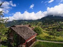Όμορφη πανοραμική άποψη καρτών του γραφικού αγροτικού τοπίου βουνών στις Άλπεις με τα παραδοσιακά παλαιά αλπικά σαλέ βουνών Στοκ φωτογραφίες με δικαίωμα ελεύθερης χρήσης