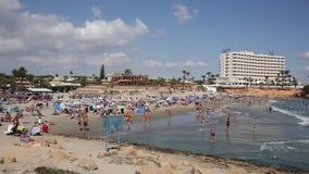 Όμορφη παραλία Λα Zenia Ισπανία με τους ανθρώπους στη θάλασσα στην ηλιοφάνεια απόθεμα βίντεο