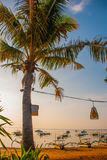 Όμορφη παραλία με έναν καφέ σε Sanur με τους τοπικούς παραδοσιακούς φοίνικες βαρκών στο νησί του Μπαλί στην αυγή Ινδονησία στοκ φωτογραφία