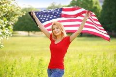 Όμορφη πατριωτική νέα γυναίκα με τη αμερικανική σημαία Στοκ Φωτογραφία