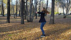 Όμορφη περιστροφή γυναικών μεταξύ των πεσμένων φύλλων στο πάρκο φθινοπώρου σε αργή κίνηση 4k 60fps Κορίτσι σε ένα παλτό που περπα απόθεμα βίντεο