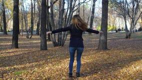 Όμορφη περιστροφή γυναικών μεταξύ των πεσμένων φύλλων στο πάρκο φθινοπώρου σε αργή κίνηση 4k 60fps Κορίτσι σε ένα παλτό που περπα φιλμ μικρού μήκους