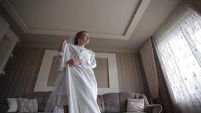 Όμορφη περιστροφή νυφών γύρω με το γαμήλιο φόρεμα στο σπίτι Υπόβαθρο του μεγάλου παραθύρου φιλμ μικρού μήκους