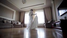 Όμορφη περιστροφή νυφών γύρω στο γαμήλιο φόρεμα στο σπίτι Υπόβαθρο του μεγάλου παραθύρου απόθεμα βίντεο