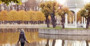 όμορφη περπατώντας γυναίκ&alph Κορίτσι πέρα από το εποχιακό υπόβαθρο φθινοπώρου Στοκ εικόνα με δικαίωμα ελεύθερης χρήσης
