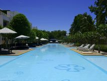Όμορφη πισίνα στο θέρετρο ξενοδοχείων με την ομπρέλα και την καρέκλα γύρω Στοκ Εικόνα