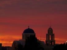 Όμορφη πορτοκαλιά και πορφυρή μεταλαμπή ηλιοβασιλέματος πέρα από την εκκλησία ύφους των Κυκλάδων, νησί Santorini της Ελλάδας Στοκ φωτογραφίες με δικαίωμα ελεύθερης χρήσης