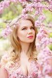 Όμορφη πράσινος-eyed γυναίκα που κρατά έναν ανθίζοντας κλάδο κερασιών στα χέρια Στοκ Εικόνες