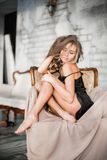 Όμορφη προκλητική γυναίκα με τα ξανθά μαλλιά στην κομψή μαύρη συνεδρίαση φορεμάτων στην πολυθρόνα στο δωμάτιο Στοκ φωτογραφίες με δικαίωμα ελεύθερης χρήσης
