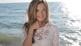 Όμορφη προκλητική γυναίκα με τα ξανθά μαλλιά στην κομψή τοποθέτηση φορεμάτων στην παραλία, που χαμογελά στη κάμερα φιλμ μικρού μήκους