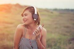 Όμορφη προκλητική γυναίκα με την μπλε μουσική ακούσματος φορεμάτων μόνιμη μέσα Στοκ Φωτογραφίες